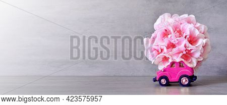 Pink Toy Car Delivering Flowers Bouquet On Gray Background. Copy Space. Flower Delivery, Birthday, V