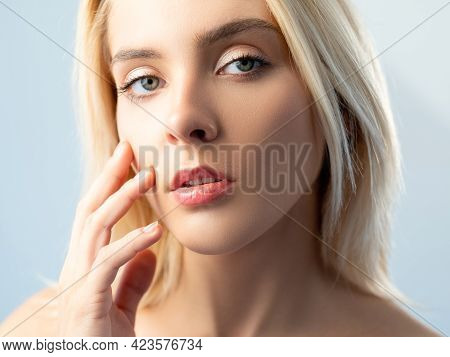 Facial Care. Skin Moisturizing. Freshness Beauty. Confident Blonde Woman With Nude Makeup Touching S