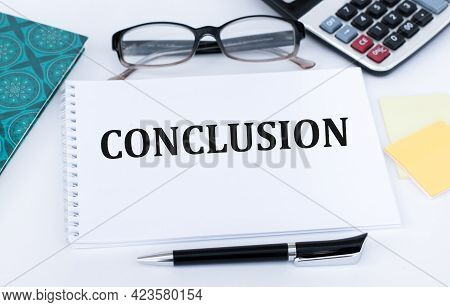 Business Concept, On The Table Notepad With The Text Of The Conclusion
