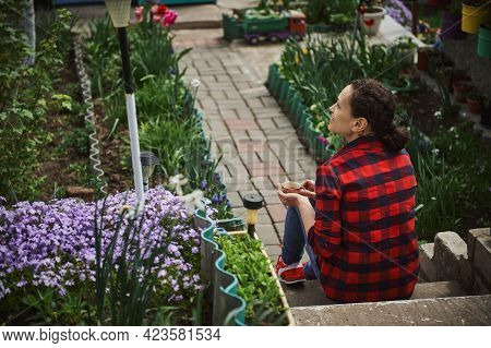 Beautiful Mature Hispanic Woman Gardener Resting Outside Country House. The Concept Of A Calm Outdoo