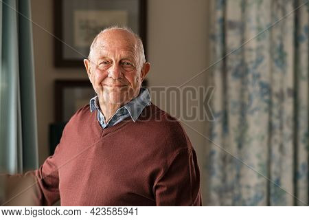 Portrait of happy retired senior man standing at home near window. Satisfied old man looking at camera and smiling while standing near the window. Positive and confident elderly enjoy his retirement.