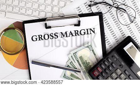 Text Gross Margin On Office Desk Table With Keyboard, Dollars,calculator ,supplies,analysis Chart On