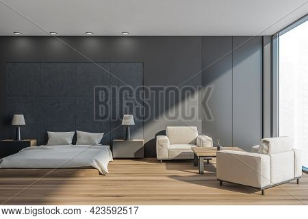 Dark Bedroom Interior With Grey Bed And Pillows, Parquet Floor And Two Armchairs With Coffee Table.