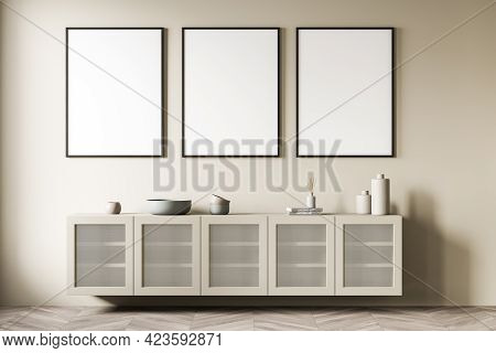 Beige Art Room Interior With Long Wooden Commode With Books And Vase On Parquet Floor. Three Blank F