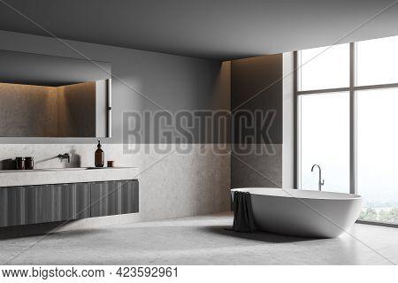 Dark Bathroom Interior With White Bathtub And Sink With Bath Accessories, Side View. Minimalist Room
