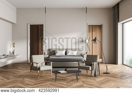 Wooden And White Bedroom Interior With Bed And Linens, Parquet Floor And Two Seats With Coffee Table