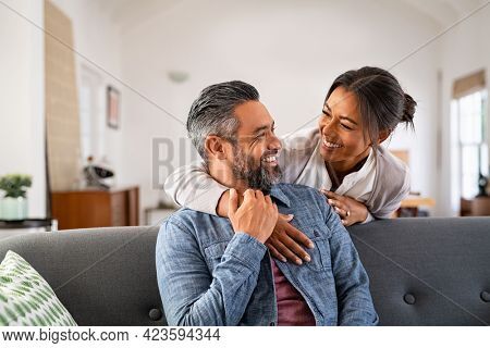 Smiling ethnic woman hugging her husband on the couch from behind in the living room. Middle eastern man having fun with his beautiful young wife on the couch. Mid adult indian man with latin woman.