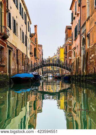 Boats docking close to a Beautiful small bridge in Venice
