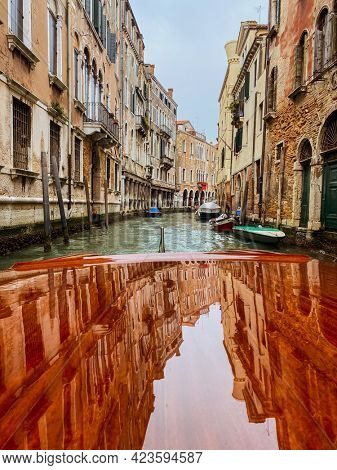 Houses reflections on the Varnished wooden hood, pontoon, of the water taxi in the streets of Venice, which leaves