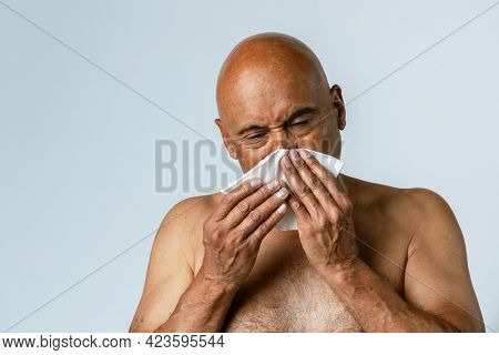 Coronavirus infected senior man blowing nose into a tissue paper