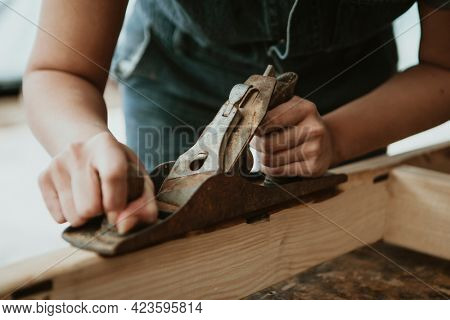 Female carpenter shaping lumber with a hand plane