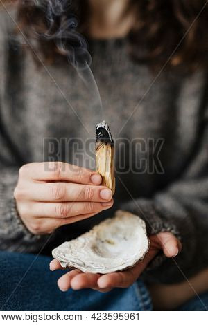 Woman buring palo santo for cleansing her home