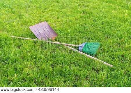 A Rusty Shovel And An Emerald-colored Broom Lie On The Green Grass In The Park. Garden Tools