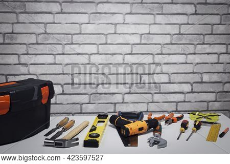 Set Of Various Work Tools And Toolbox On Grey Surface Near Brick Wall With Copy Space.