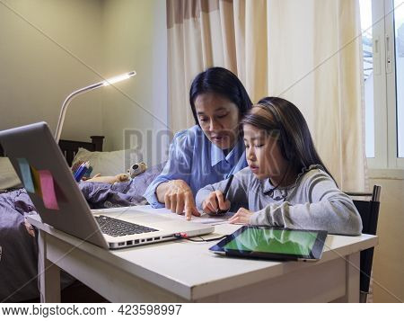 Asian Young Little Girl Using Pencil To Do Homework With Her Mother. Student Kid Writing  Homework B