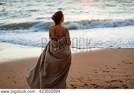 Beautiful Young Woman Wrapped In A Blanket. The Girl On The Seashore In The Evening Stands. Lonely L