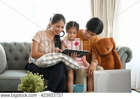 Family Using Digital Tablet. Parents Showing Digital Tablet To Their Daughter On Couch At Home.