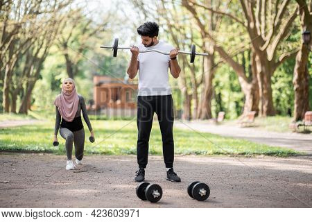 Handsome Muslim Guy Using Barbell For Training Arms While Woman In Hijab Workout With Barbells. Happ
