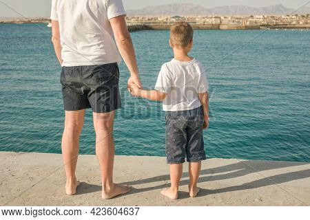 Father And  Son  Spending Time Together Sea Vacation. Little Boy And Dad Stay  On Beach And Looks Ou