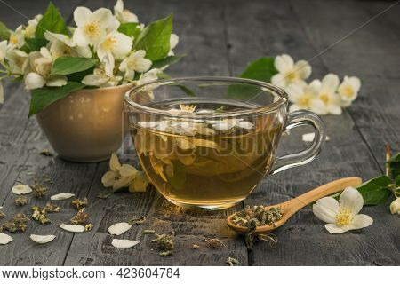 A Cup Of Jasmine Tea And Jasmine Flowers On A Wooden Table. An Invigorating Drink That Is Good For Y
