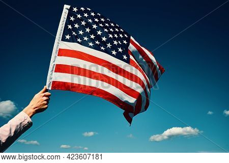 Waving American Flag Outdoors. Hand Holds Usa National Flag Against Blue Cloudy Sky. 4th July Indepe