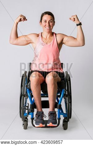 Athlete in a wheelchair flexing her arms
