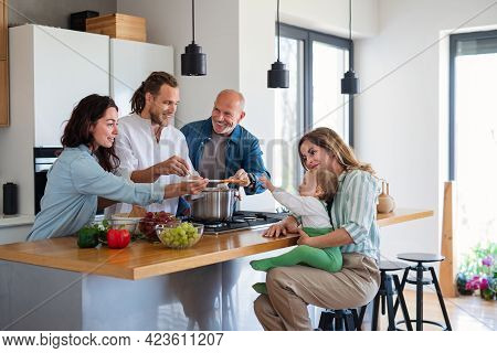 Happy Multigeneration Family With Baby Indoors At Home Cooking.