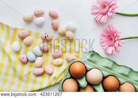 Chocolate Easter eggs and pink gerbera flowers flat lay
