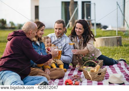 Happy Multigeneration Family Outdoors Having Picnic In Backyard Garden.