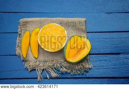 Top View Of Ripe Mango Pulp And Cuts On Burlap Fabric Isolated On Wooden Background With Copy Space