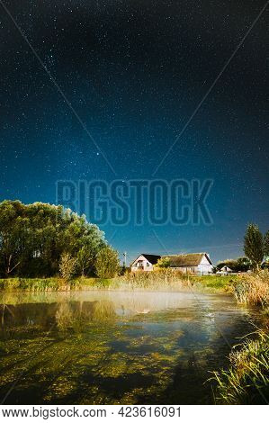 Evaporation Over River Lake Near Houses In Village. Milky Way Galaxy In Night Starry Sky Above Lake