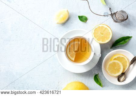 Lemon Tea In A Cup, Shot From The Top With Copy Space. Organic Lemons, Green Leaves And The Natural