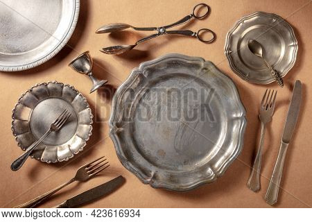 Vintage Silver Tableware, Overhead Flat Lay Shot On A Rustic Background. Many Different Plates And D