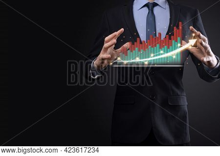 Businessman On A Black Background Presses, Presses A Finger On A Positive Growth Arrow. Graphs Of In