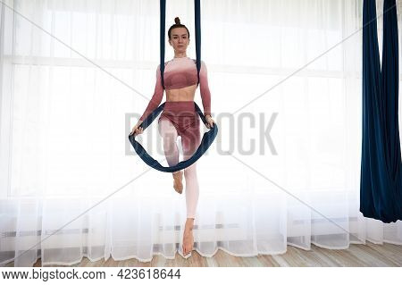 Beautiful, Athletic Woman In A Top And Leggings Performs Antigravity Yoga Exercises In A Spacious He