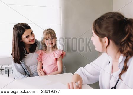 Mother Or Sister With Small Little Girl Visiting Hospital For The Family Doctor Visit In The Clinic.
