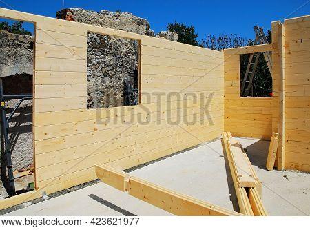 Empty Front Door And Wondow Frames Inside A Partially Constructed Wood (fir) Block House, A Pre-cut