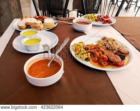 White Plates With Food On The Table In A Turkish Hotel Restaurant. Tomato Soup, Rice With Stewed Veg
