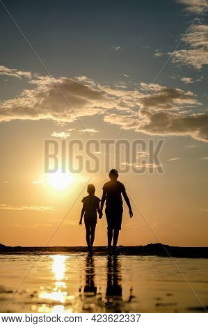Silhouette Of Two Sisters Holding Hands Who Standing On The Beach At The Sunset. Vertical Photo