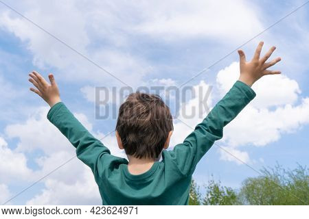 Child Boy Raising His Hands To The Blue Sky In Sunny Day In Admiration For Environment. Loving Natur