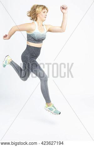 Senior Sportswoman Ideas. Running Mature Sportswoman During Active Jogging Training Indoors Against