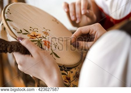 Closeup Of Hands Of Young Caucasian Woman Posing With Fancywork Hoop In Retro Dress In Rural Environ