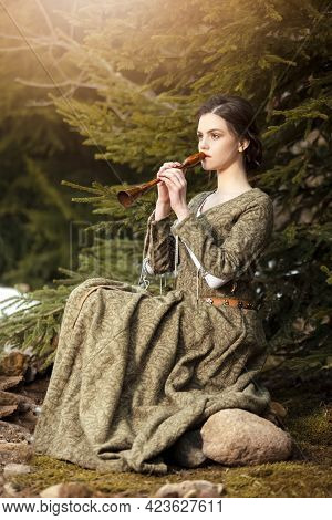Sensual Caucasian Brunette Female In Old Retro  Medieval Green Dress Playing The Flute Against Firtr