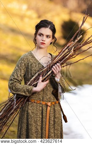 Natural Portrait Of Sensual Caucasian Female In Village Dress With Pieces Of Brushwoods In Hands Out