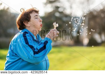 International Day Of Older Persons. Portrait Of An Elderly Caucasian Grandmother Blowing On A Dandel