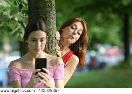 Distracted Woman Using Smart Phone Being Spied By Her Curious Friend In A Park