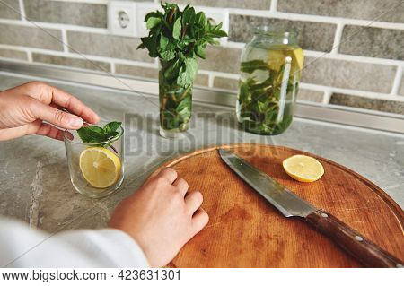 Close-up Of A Woman's Hand Tossing A Slice Of Lemon And Mint Leaves Into A Transparent Glass. Sliced