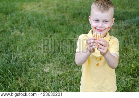 Bitten French Hot Dog In Bacon With Fried Sausage In A Child's Hand Against The Grass. Space For Tex