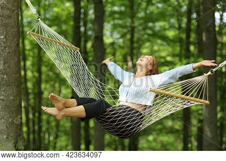 Happy Woman Swinging On Hammock Outstretching Arms In A Forest