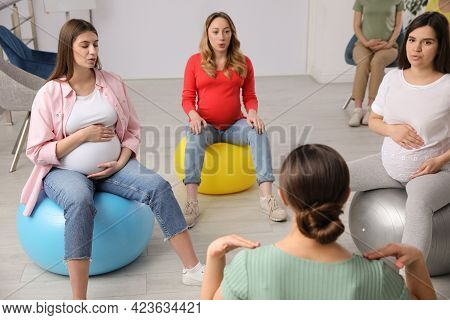 Group Of Pregnant Women With Trainer At Courses For Expectant Mothers Indoors